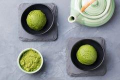 绿茶matcha在碗的冰淇凌瓢在一张灰色石背景顶视图 免版税图库摄影