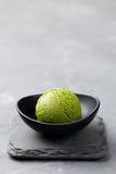 绿茶matcha在碗的冰淇凌瓢在灰色石背景 复制空间 免版税库存图片