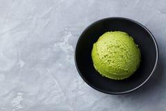 绿茶matcha在黑碗的冰淇凌瓢在灰色石背景 复制空间顶视图 免版税库存照片