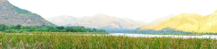 草、湖和木头桥梁的全景在北碧的山脉前面在泰国 免版税库存照片