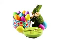 绿草与一个礼物盒的复活节兔子兔子用复活节五颜六色的鸡蛋 免版税库存图片