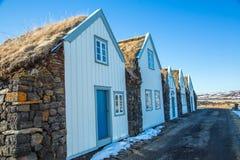 草与白色前面的屋顶小屋 库存图片