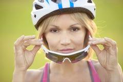 以绿草为背景的妇女骑自行车者 免版税库存照片