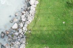草和河的岩石 免版税库存照片