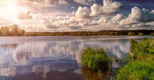 草和湖在日落期间 自然美好的横向 严重的天空 湖的意想不到的看法在sunlig下的森林里 免版税库存照片