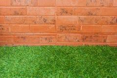 草和砖墙背景 免版税库存照片