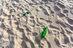 草在沙子的瓶废弃物 免版税库存图片