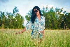 草地的美丽的年轻深色的女孩 免版税库存图片