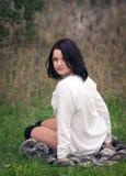 草坐的妇女年轻人 库存图片