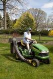 草坪人刈草机骑马 库存图片