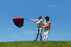 草坪人老常设伞妇女 库存照片
