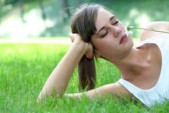 草坪位于的嗅到的妇女 库存图片