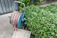 草坪和庭院的浇灌的水管 室外在夏天露台 小连栋房屋四季不断的夏天庭院 奥地利维也纳 库存图片