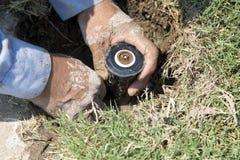草坪喷水隆头修理 免版税图库摄影