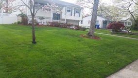 草坪好的裁减刈草机房子郊区 免版税图库摄影
