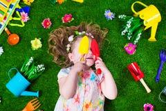 草坪的小女孩有园艺工具的 免版税库存照片