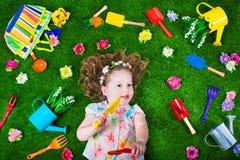 草坪的美丽的女孩有园艺工具的 免版税库存照片