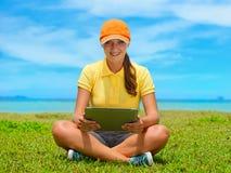 草坪的美丽的少妇有她的片剂计算机的 免版税图库摄影