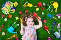 草坪的逗人喜爱的小女孩有园艺工具的 库存图片