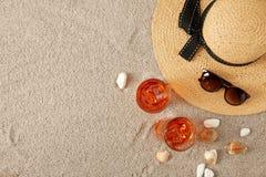 草帽、鸡尾酒、贝壳和太阳镜顶视图在沙子 图库摄影