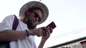 草帽和太阳镜的一年轻人使用他的智能手机在街道 股票视频