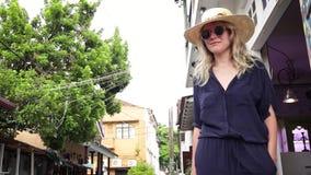 草帽和时髦太阳镜的一名年轻美丽的白肤金发的妇女 股票录像