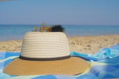 草帽和海胆毛巾和沙子的在岸附近在一个海滩在夏天 免版税库存图片