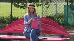 草帽和牛仔裤的女孩坐与一个明亮的笔记薄的一条长凳 股票录像