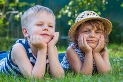 草帽和男孩的,夏令时假期微笑的小女孩 免版税库存图片