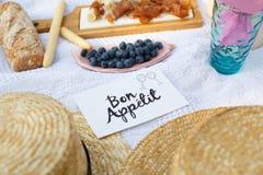 草帽在一条白色野餐毯子放置在标识牌好的妙语apetit明亮的夏日背景旁边 夏天过周末休闲 免版税库存图片