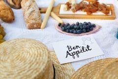草帽在一条白色野餐毯子放置在标识牌好的妙语apetit明亮的夏日背景旁边 夏天过周末休闲 库存照片