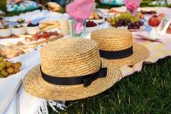 草帽在一条白色野餐毯子放置在绿色草坪明亮的夏日背景 夏天过周末休闲 免版税库存图片
