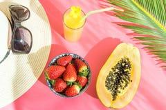 草帽太阳镜高玻璃的平的位置安排与新鲜的柑橘热带水果汁番木瓜棕榈叶的在桃红色背景 免版税库存图片