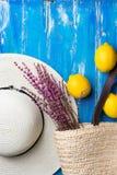 草帽柳条手织的海滩袋子用在深蓝木背景的淡紫色枝杈新鲜的柠檬 旅行假期时尚 库存图片
