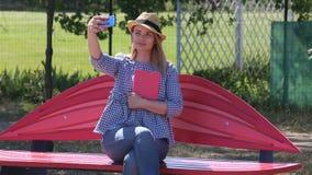 草帽的一个女孩坐一张公园长椅在夏天并且为照相在电话 股票录像