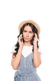 草帽的严肃的少妇谈话在智能手机 免版税库存图片