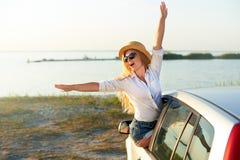 草帽的俏丽的妇女享受在的旅行夏天休假 举她的汽车的手的激动的年轻女性 库存照片