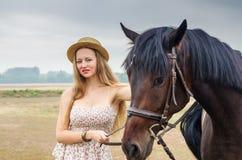草帽的女孩和夏天穿戴,摆在与马 图库摄影
