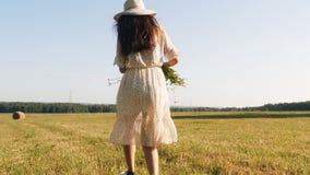 草帽的妇女有跑在草甸的花的 股票录像