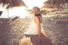 草帽的少妇坐一个热带海滩,享受沙子和日落 放置在棕榈树遮阳伞树荫下  库存照片