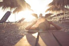 草帽的少妇坐一个热带海滩,享受沙子和日落 放置在棕榈树遮阳伞树荫下  库存图片