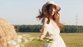 草帽的年轻女人有花的在草甸转动在周围 股票录像