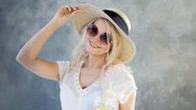 草帽的年轻美丽的白肤金发的妇女 夏天样式太阳镜 图库摄影