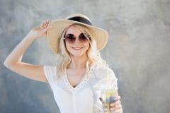 草帽的年轻美丽的白肤金发的妇女 夏天样式太阳镜 免版税库存图片