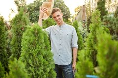 草帽的微笑的人花匠在有很多thujas的托儿所庭院里站立在一温暖的好日子 免版税库存图片