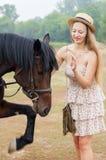 草帽的快乐的金发碧眼的女人和夏天穿戴与马 免版税库存照片