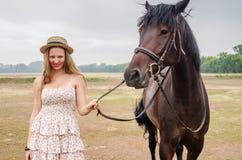 草帽的快乐的金发碧眼的女人和夏天穿戴,拍摄与马 免版税库存图片