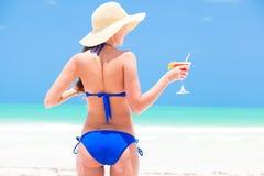 草帽的愉快的少妇有鸡尾酒的  免版税库存图片