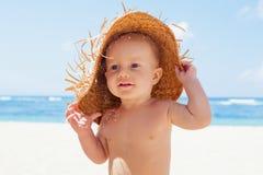 草帽的愉快的男婴在晴朗的热带海滩 免版税库存照片