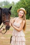 草帽的美丽的女孩和夏天穿戴摆在与马 免版税库存图片